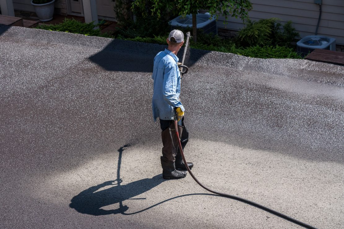 Worker applying blacktop sealcoat to asphalt street using a spray to provide a protective coat against the elements